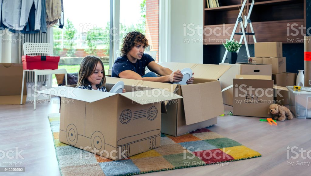 Father and son playing car racing with cardboard boxes stock photo