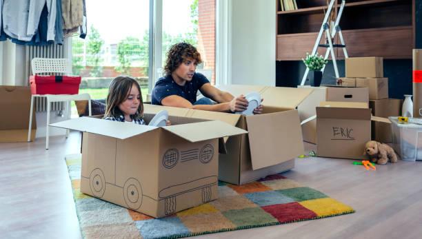 Vater und Sohn spielen Autorennen mit Kartons – Foto