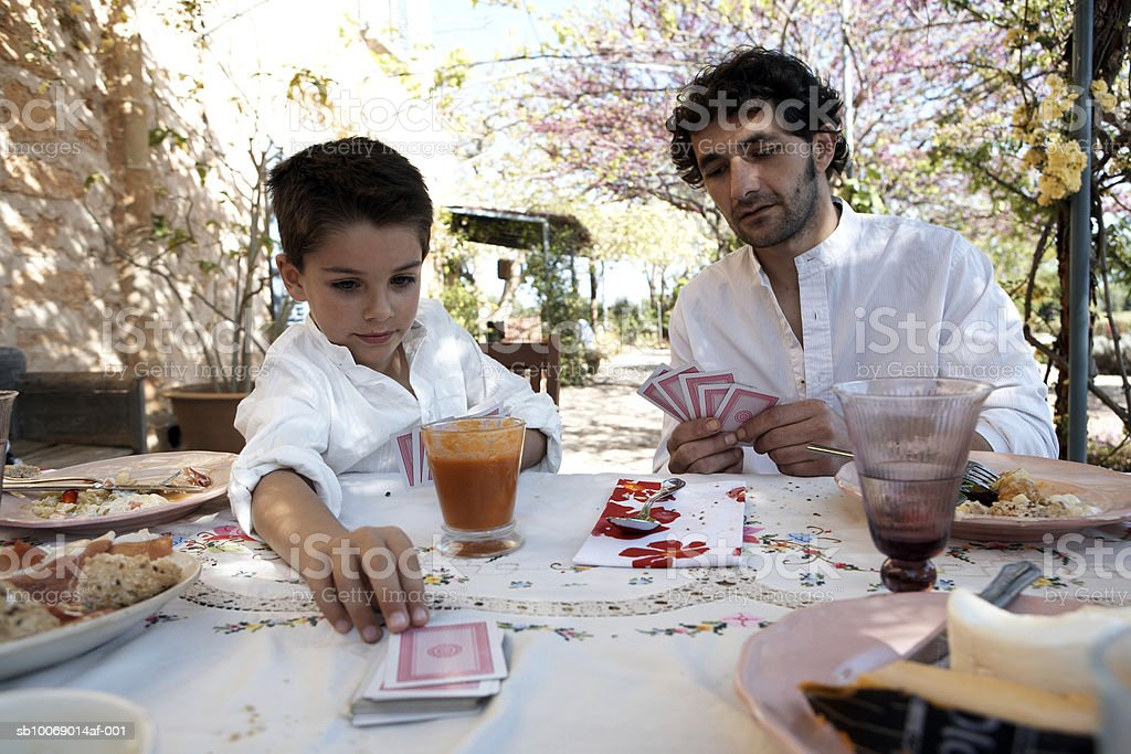 Father and son (8-9) playing cards on outdoor dining table royalty free stockfoto