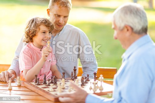 Little boy with the help of his father playing chess with his grandfather, on a sunny day outdoors