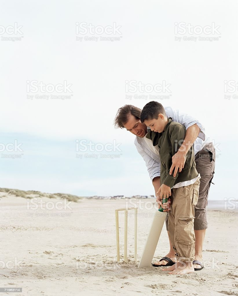 Father and son playing cricket stock photo