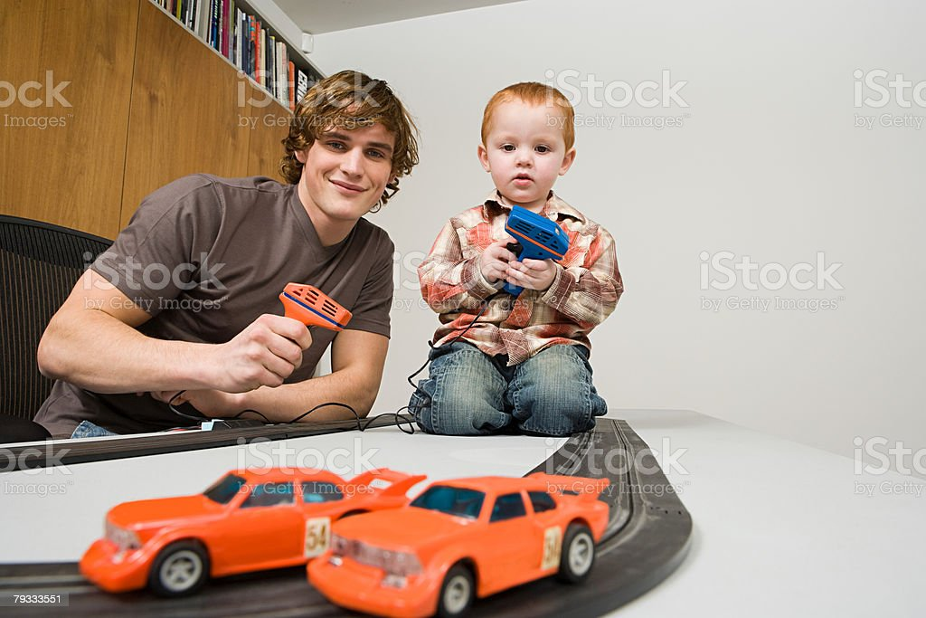 Father and son playing electric shot car royalty-free stock photo