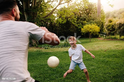 Father and son playing football in backyard garden. Happy little boy playing football with his father.