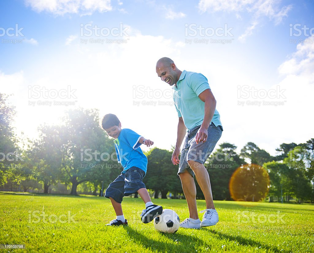 Father and son playing football together royalty-free stock photo