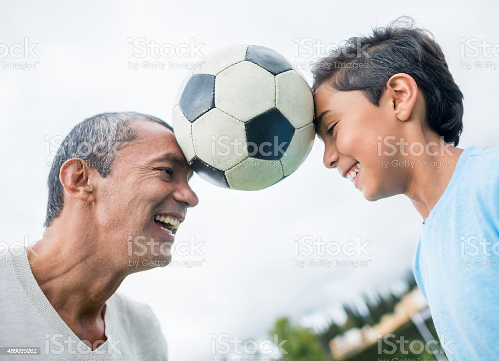 Father and son playing football together stock photo