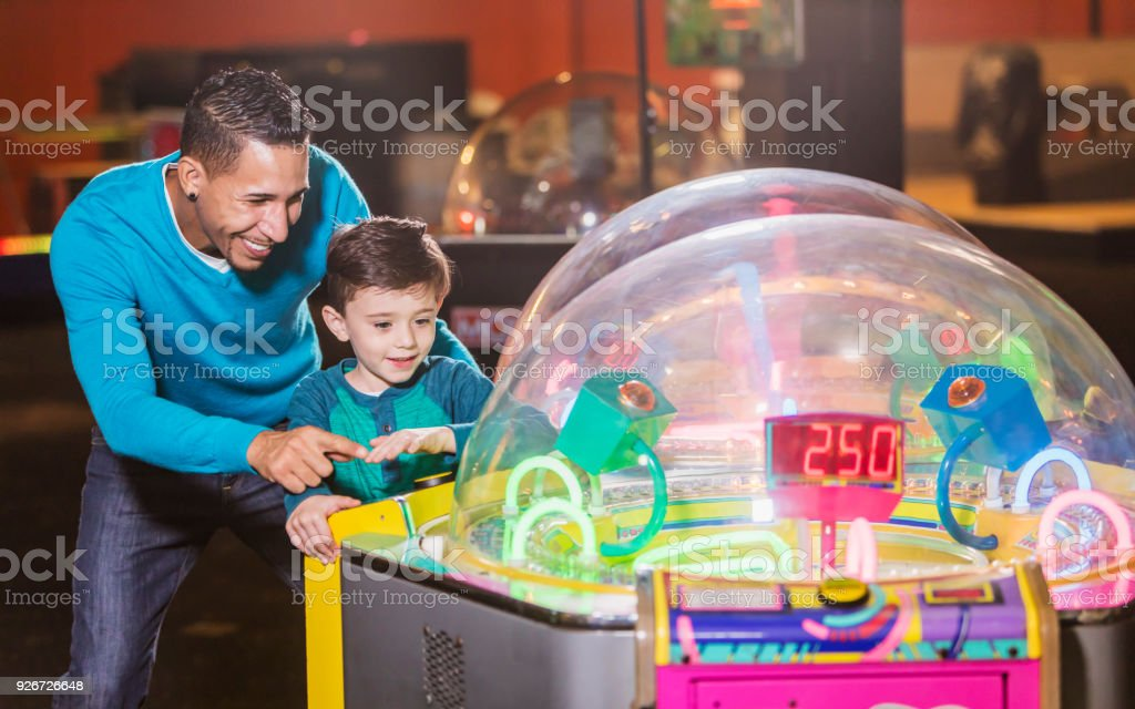 Father and son playing game in amusement arcade stock photo