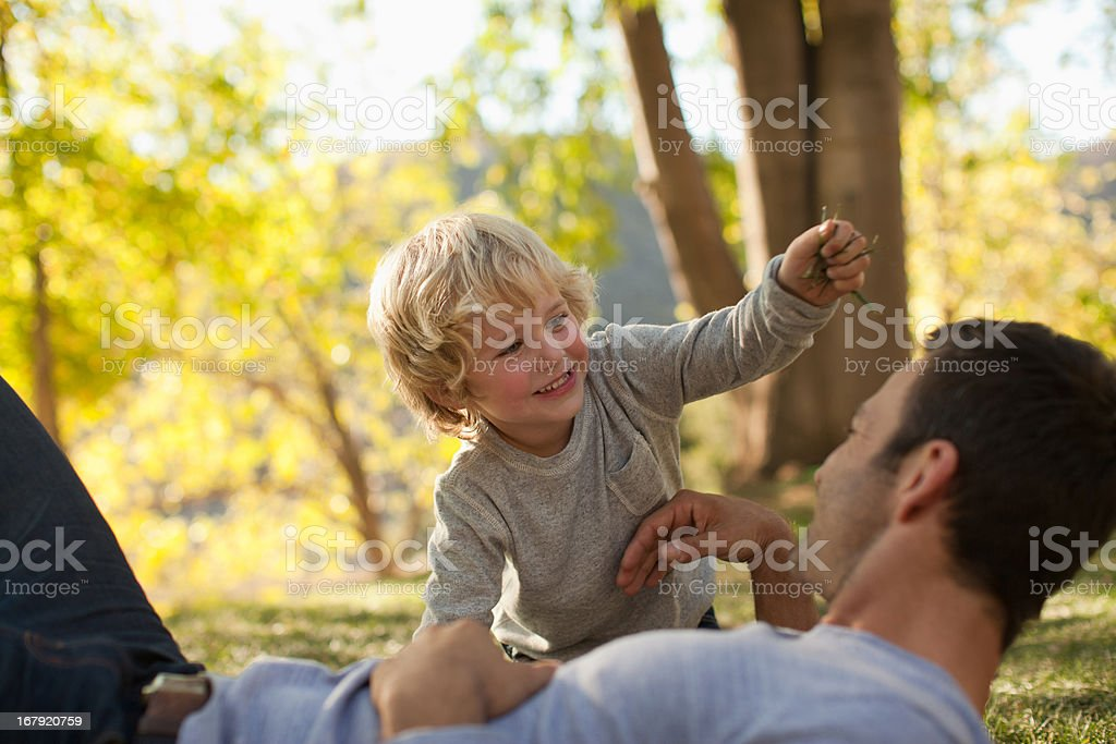 Father and son playing in grass royalty-free stock photo