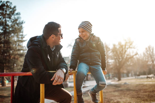 Father and son playing in park stock photo