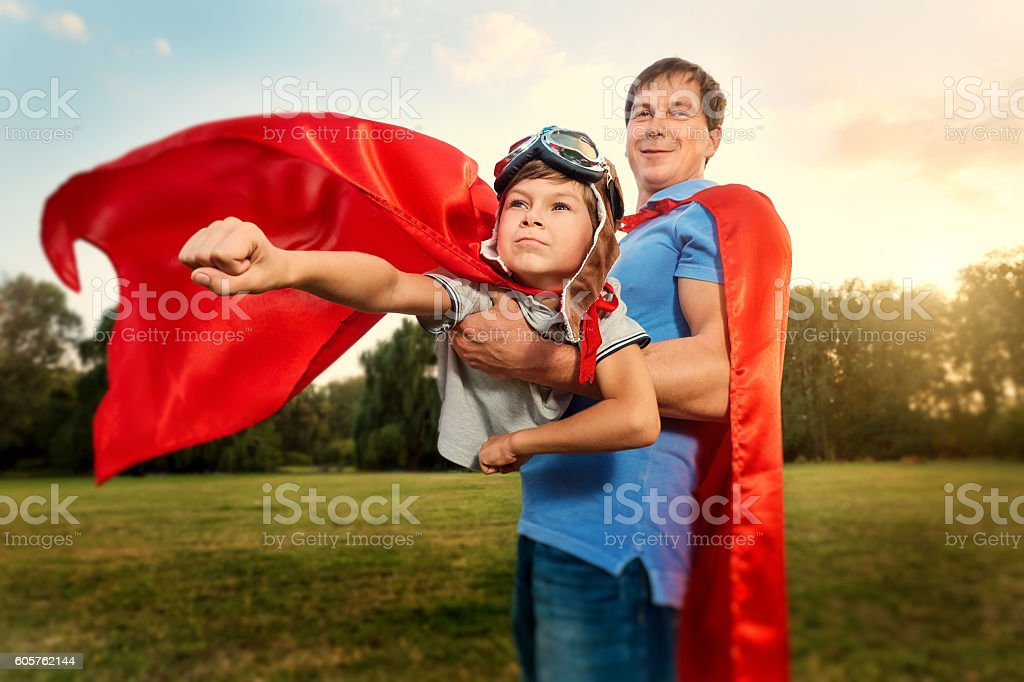 Father and son playing in superhero costumes  park on natu stock photo