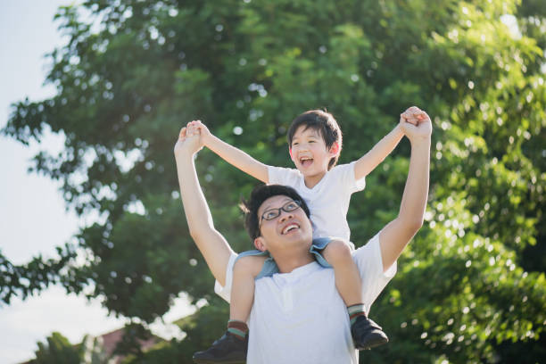 Father and son playing in the park stock photo