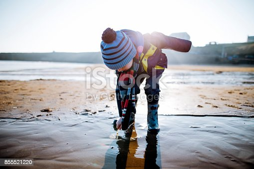 Young man enjoying walking along the coast. Its cold outside so they are wrapped up warm. The man is squatting down to play in the sand as he sits