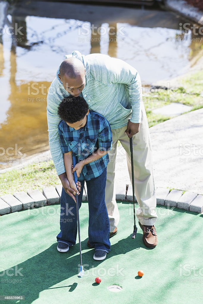 Father and son playing miniature golf royalty-free stock photo