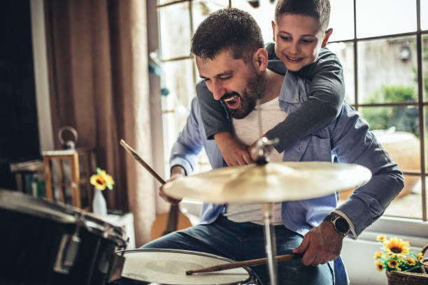 Father and son playing musical instruments at home