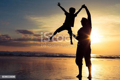 586180632istockphoto Father and son playing on the beach at the sunset. 606633696
