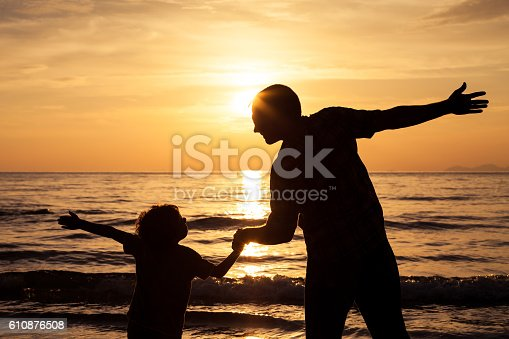 586180632istockphoto Father and son playing on the beach at the sunset. 610876508