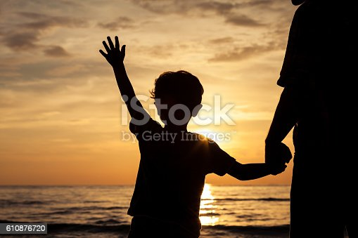 586180632istockphoto Father and son playing on the beach at the sunset. 610876720