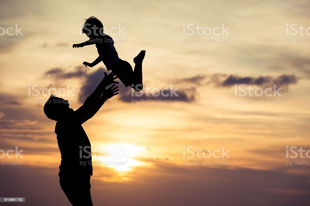 Father and son playing on the beach at the sunset. stock photo