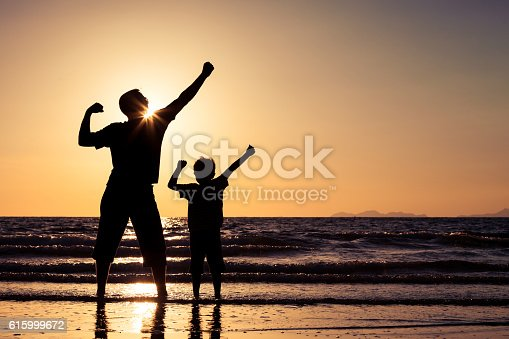 586180632istockphoto Father and son playing on the beach at the sunset. 615999672