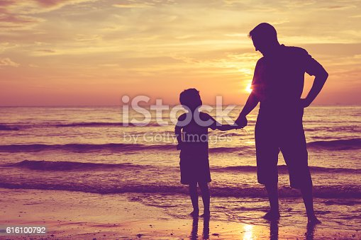 586180632istockphoto Father and son  playing  on the beach. 616100792