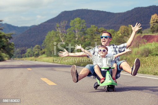 586180632istockphoto Father and son playing on the road. 586180632