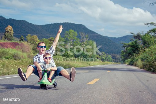 586180632istockphoto Father and son playing on the road. 586197370