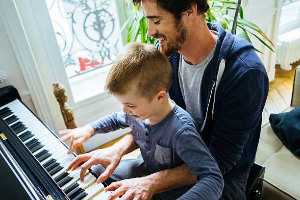 vater und sohn spielt zuhause klavier spielen zu hause - französisch übungen stock-fotos und bilder