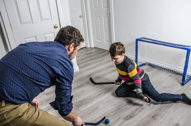 Vater und Sohn Hockeyspielen kleine Terrasse im Keller – Foto