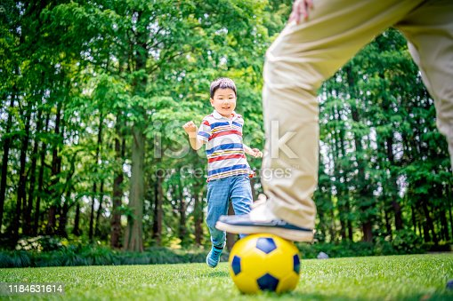 589135214 istock photo Father and son playing soccer at the public park 1184631614