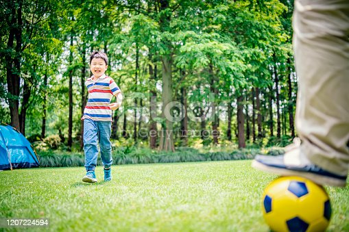 589135214 istock photo Father and son playing soccer at the public park 1207224594