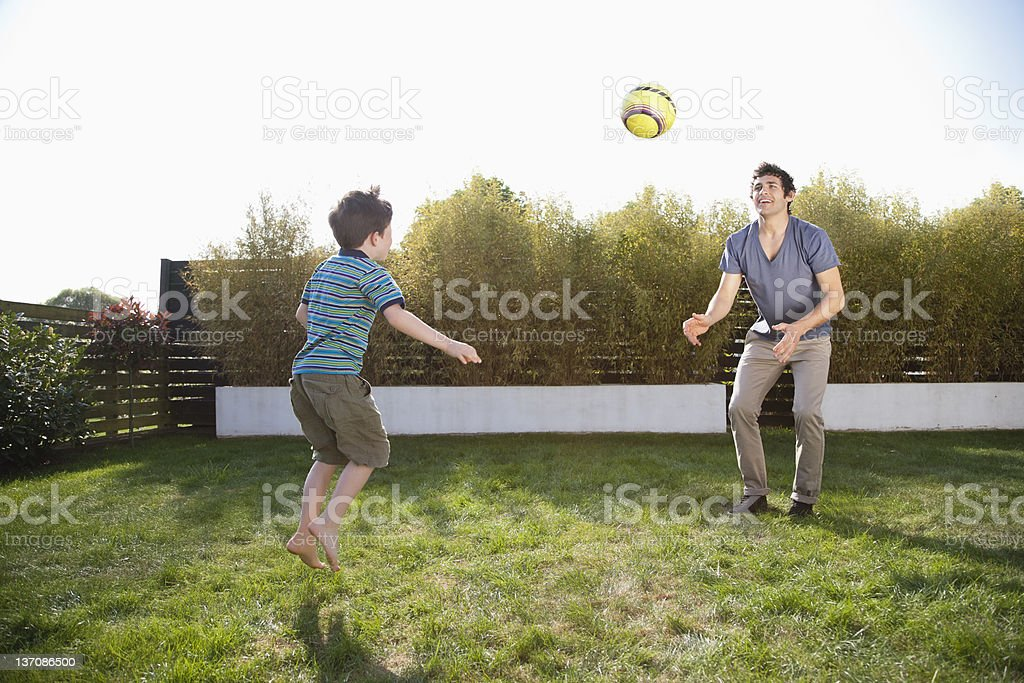 Father and son playing soccer in backyard stock photo