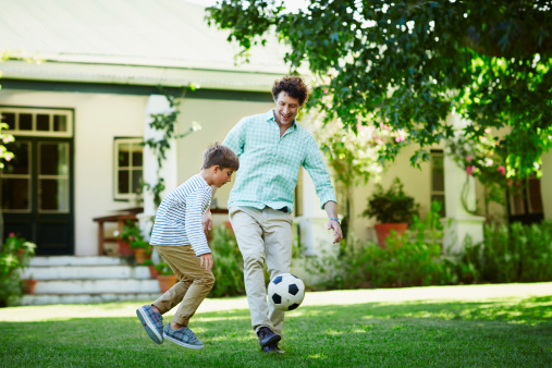 istock Father and son playing soccer in lawn 492275755