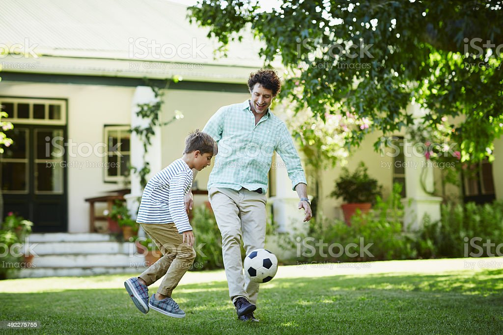 Father and son playing soccer in lawn stock photo