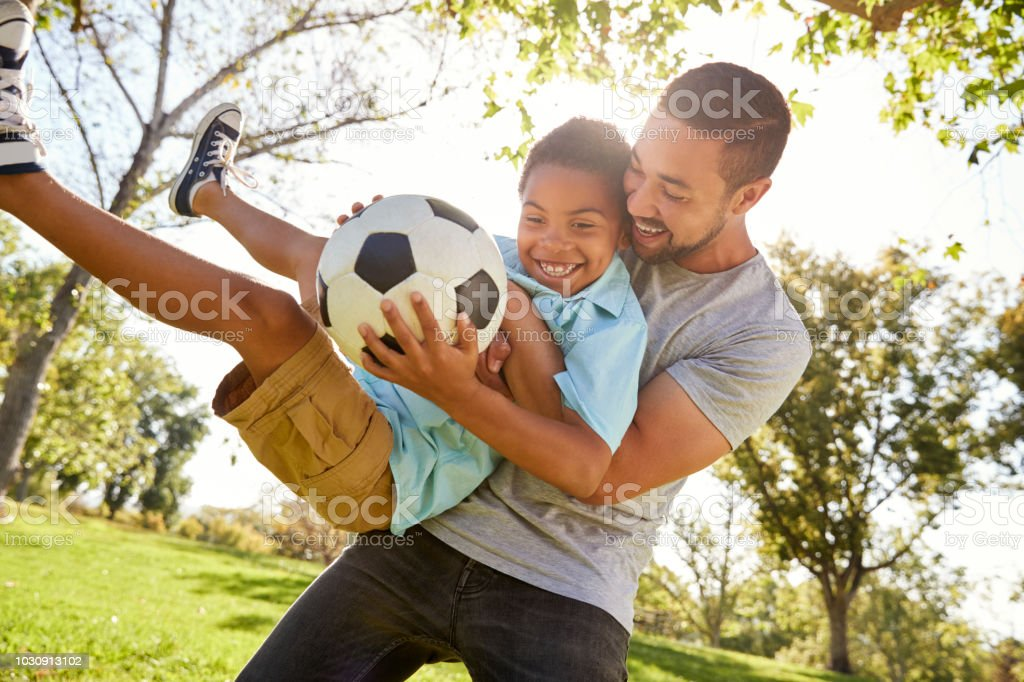 Father And Son Playing Soccer In Park Together stock photo