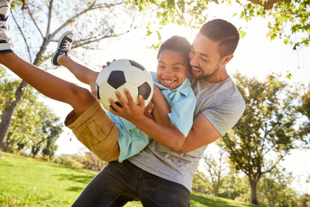 Father And Son Playing Soccer In Park Together Father And Son Playing Soccer In Park Together father stock pictures, royalty-free photos & images