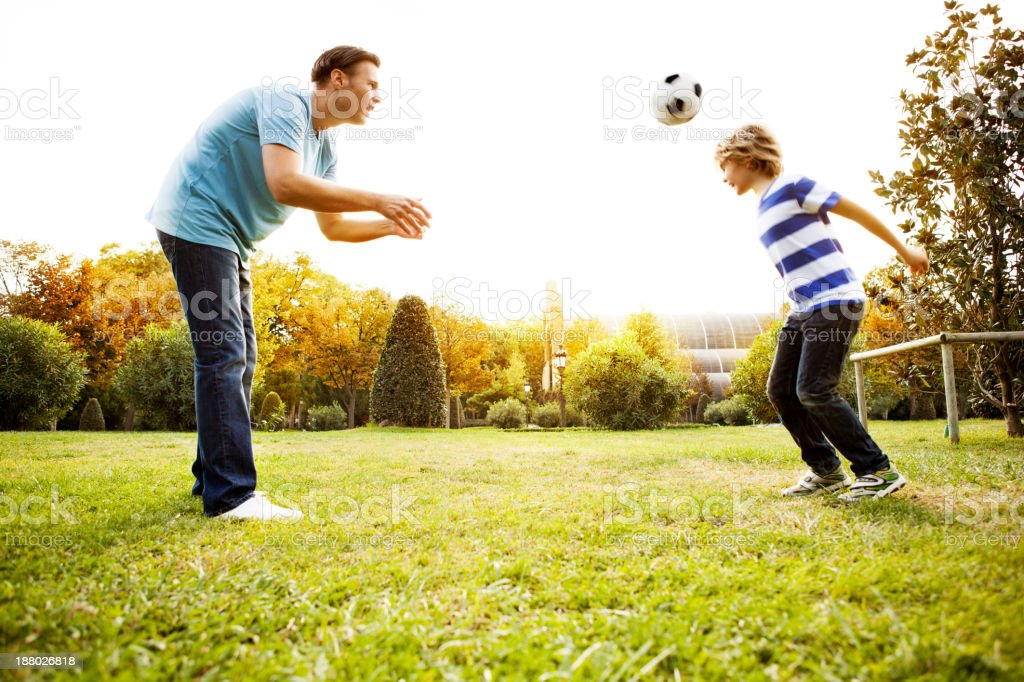 Father and son playing soccer stock photo