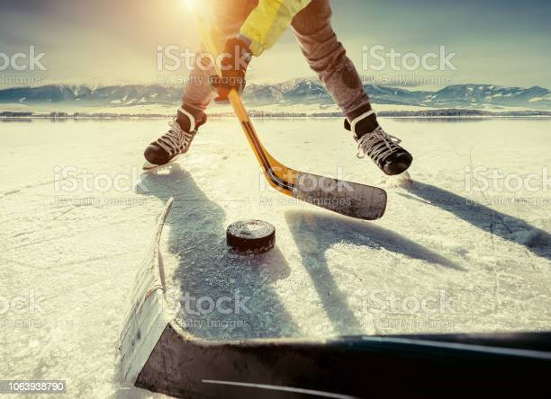 Photo of Father and son playing the hockey on the frozen high mountain lake ice.
