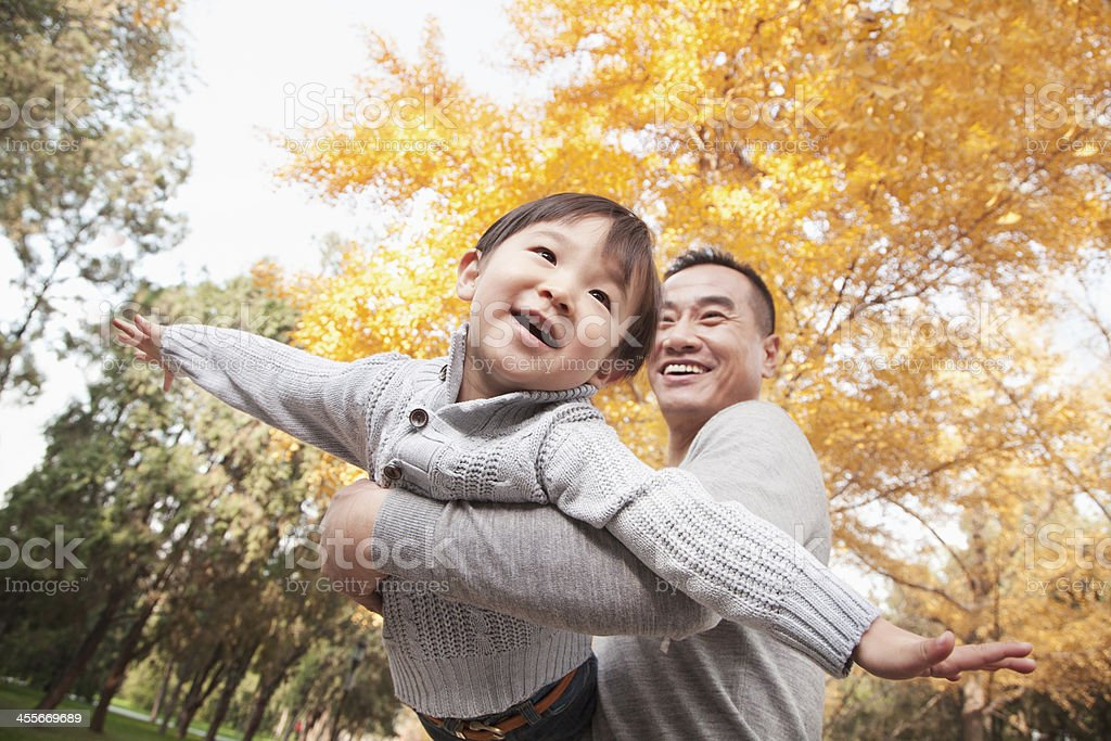Father and son playing together at the park in autumn stock photo