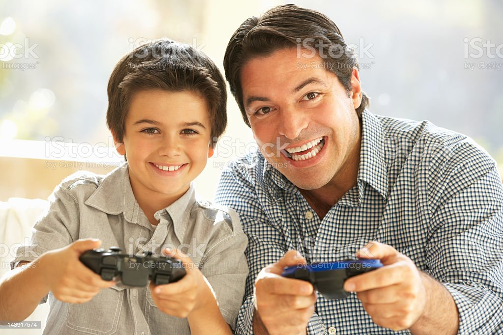 Father And Son Playing Video Game At Home stock photo