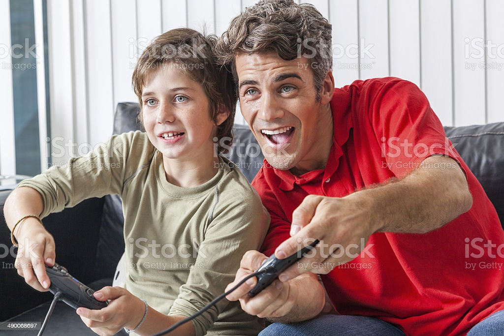 father and son playing video game stock photo