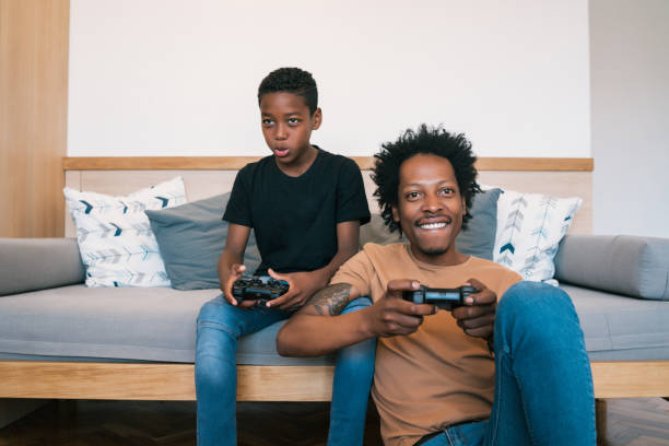 Father and son playing video games together at home. stock photo