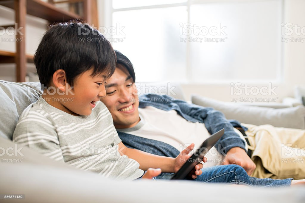 Father and son playing with a digital tablet together stock photo