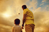 Kite flying in the sky. Father and son playing with a kite at sunset.