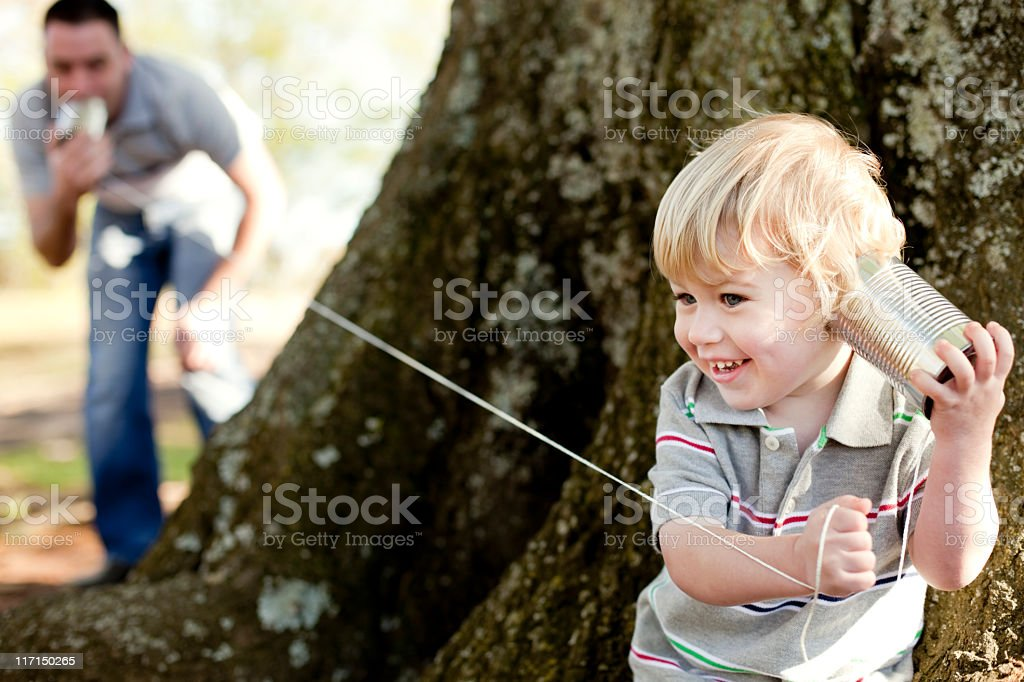 Father and son playing with a tin can telephone in the park stock photo