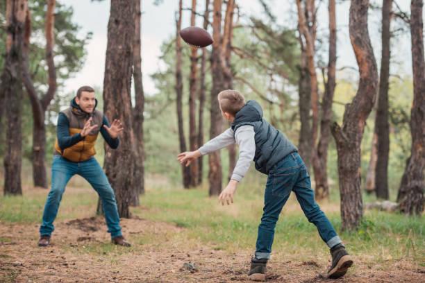 père et fils jouant avec ballon en forêt - Photo