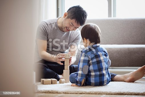 istock Father and son playing with building blocks together 1053936490