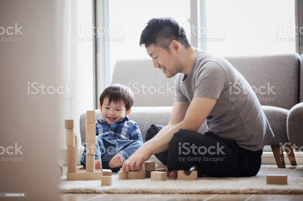 Father and son playing with building blocks together stock photo