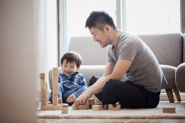 Father and son playing with building blocks together Asian father and son playing a brick sitting on floor. father stock pictures, royalty-free photos & images