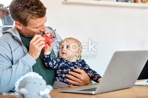 Father and baby boy playing with elephant toy with laptop on table. Mid adult man is spending leisure time with son at home. They are wearing casuals.