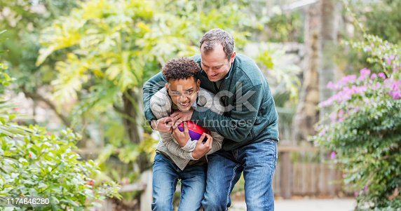 A mid adult man in his 30s playfully tackling his 12 year old mixed race African-American and Caucasian son. The boy is hugging a football.