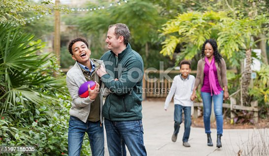 1091098220 istock photo Father and son playing with football 1197188035
